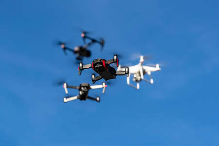 A group of drones fly through the air against a blue sky