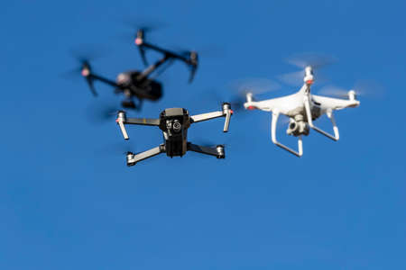 A group of drones fly through the air against a blue sky Editorial