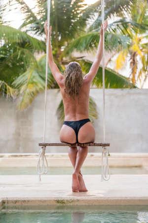 A beautiful blonde model swings by the pool in the Yucatán Peninsula near Merida, Mexico