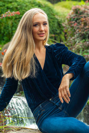 A gorgeous blonde model poses outdoors in her fall clothes