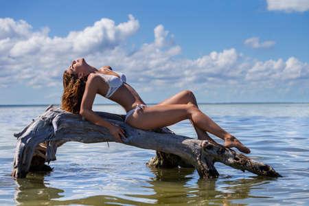 A beautiful hispanic brunette model enjoys the summer weather on a Caribbean beach
