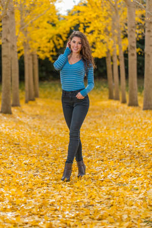 A beautiful brunette model with yellow fall foliage