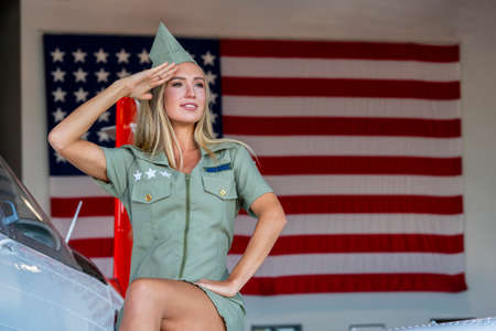 A beautiful blonde model poses with a vintage WWII aircraft