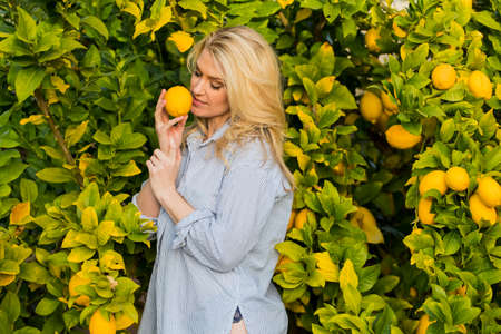 Blonde model posing outdoors with fruit from a lemon tree