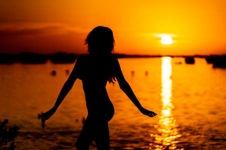 A beautiful latin model is silhouetted as she poses with the rising sun behind her on a exotic Caribbean beach Banque d'images