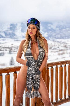 A gorgeous brunette model poses outdoors near the ski slopes Standard-Bild