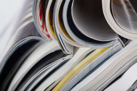 Numerous magazines spread out against a white background in a studio environment