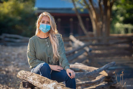 A gorgeous blonde model poses outdoors in her fall clothes wearing a mask during the COVID-19 Pandemic