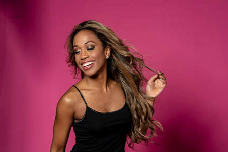 Gorgeous African American  model posing against a pink background