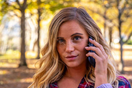 A gorgeous blonde model talks on her cellphone on an autumn day outdoors in a park