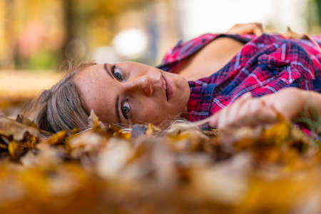A gorgeous blonde model enjoys a Autumn day outdoors in a park