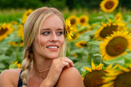 A gorgeous blonde model poses outdoors in a field of sunflowers while enjoying a summers day