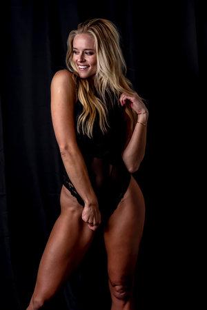 A beautiful blonde lingerie model posing in a studio environment