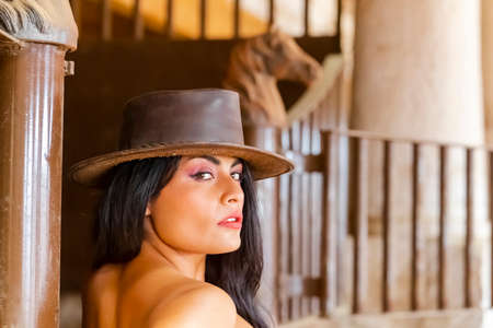 A gorgeous Hispanic Brunette model poses with a horse outdoors in a Mexican stable
