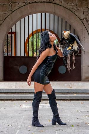 A gorgeous Hispanic Brunette model poses outdoors with a Caracara bird outdoors at a hacienda Zdjęcie Seryjne