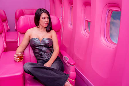 A beautiful asian model sits in a pink airplane ready for her next adventure