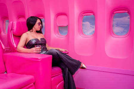 A beautiful asian model sits in a pink airplane ready for her next adventure Archivio Fotografico