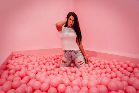 A beautiful asian model plays in a colorful room with a huge amount of plastic balls Archivio Fotografico