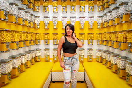 A beautiful asian model poses in a room full of gum ball machines