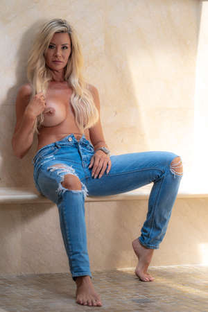 A gorgeous blonde model poses topless lounging around in a home environment Archivio Fotografico