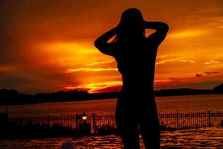 A beautiful Hispanic Brunette swimsuit model enjoys a sunset on a beach in California Archivio Fotografico