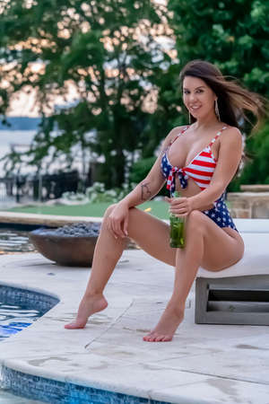 Portrait of a woman wearing a patriotic American bikini while enjoying a sunset on a summers night Archivio Fotografico