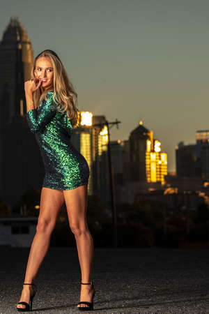 A gorgeous blonde model poses outdoors in her evening dress