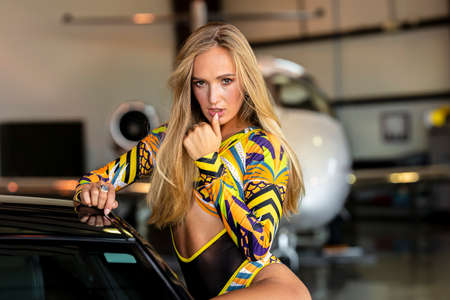 A gorgeous blonde model poses with an American muscle car inside an aircraft hangar