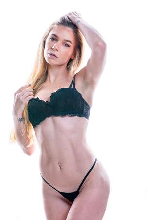An attractive blonde lingerie model poses in a studio environment Archivio Fotografico