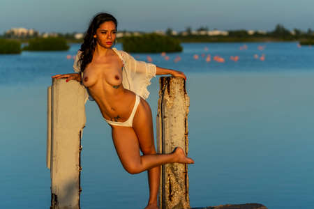 A beautiful latin model poses with the rising sun on a exotic Caribbean beach