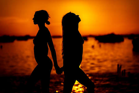 Two beautiful latin models are silhouetted against the rising sun behind them on a exotic Caribbean beach