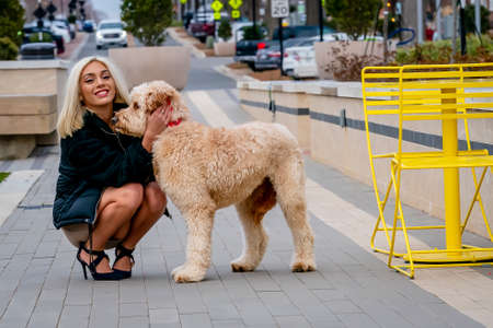 A gorgeous young blonde model poses outdoors with her young puppy