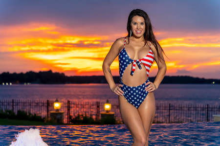 Portrait of a woman wearing a patriotic American bikini while enjoying a sunset on a summers night Stock fotó