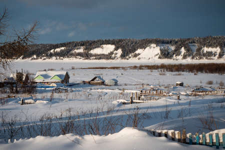 Winter landscape. Exterior view of wooden houses covered with snow in Russian village located in Siberia. Russia.