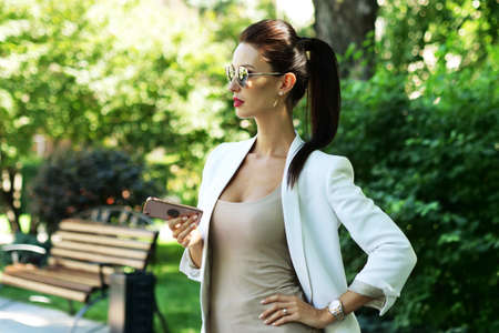 Close-up shot of beautiful young businesswoman in business suit and sunglasses holding in hands smartphone Archivio Fotografico