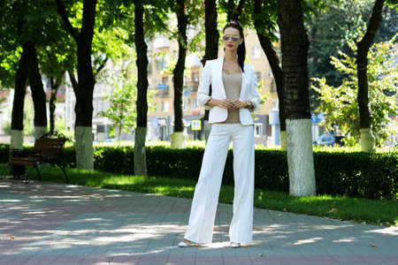 Beautiful young brunette businesswoman dressed in white business suit standing on summer street in a park and looking at camera