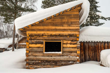 Winter landscape. Exterior view of wooden house covered with snow in Russian village located in Siberia. Russia.