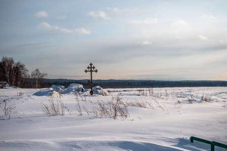 Orthodox cross standing on the snowy bank of the frozen River Yenisei in Siberia. Russia. Archivio Fotografico