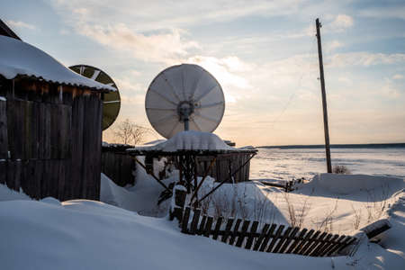 Two satellite dishes against a cloudy sky and frozen river in a Russian village with old wooden buildings. Winter landscape in Siberia. Russia.