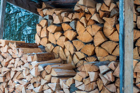 Close-up shot of chopped and sawn trunks of trees stacked in a large log woodpile in the yard. Firewood prepared for the fireplace and stove.