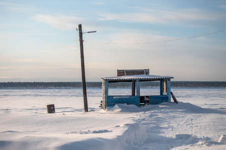 Empty pier on the shore of the frozen Yenisei river in Siberia. Russia.