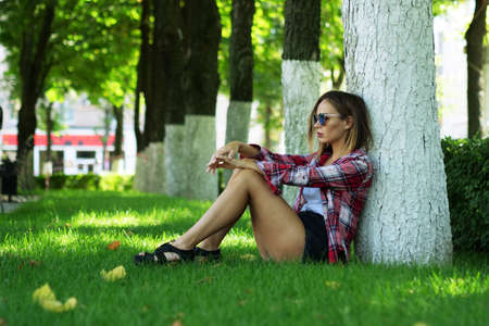 Young woman in sunglasses sitting under tree on the green grass at city park