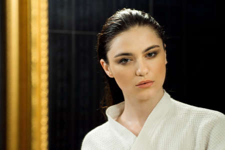 Close-up shot of an attractive young woman dressed in a white bathrobe with wet hair after a shower looking at camera in bathroom. Stock fotó