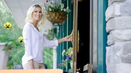 Pretty cheerful blonde smiling woman is getting into modern building by the front door.