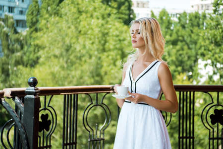 Beautiful young blonde woman in white dress drinking coffee, standing on the veranda on summer day in luxury hotel.