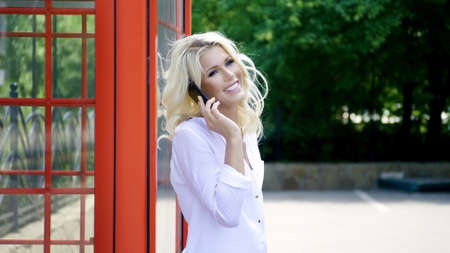 Portrait of magnificent young woman wearing white stylish shirt, having wavy blonde hair talking on a mobile phone and smiling. Фото со стока