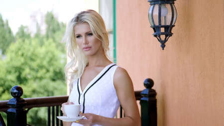 Beautiful young blonde woman in white dress drinking coffee, standing on the balcony on summer day in luxury hotel.