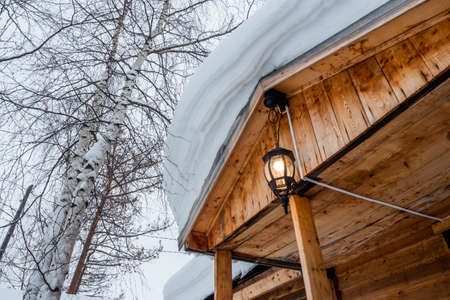 A lighted streetlight on the porch of house covered with snow in pine and birch forest. Village in winter landscape. Siberia. Russia. Фото со стока