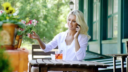 Stylish smiling blonde young woman speaking by mobile phone sitting on the veranda in a summer cafe and drinking a cold beverage.