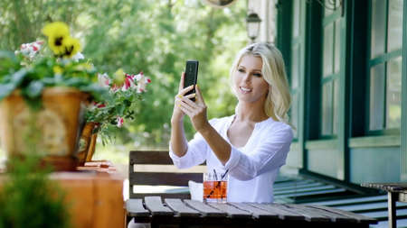 Waist up portrait of gorgeous adorable blonde woman drinking a cold lemonade sitting on the summer veranda of modern restaurant and taking a photo of herself with a smartphone to put on social media.